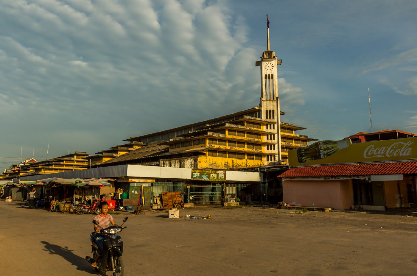 A kid on a motorbike drives past the market.