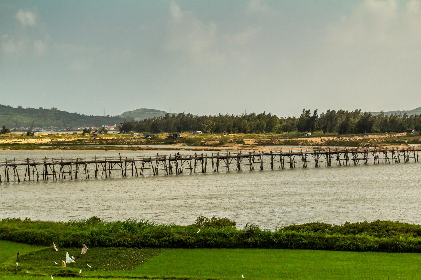Motorbikes drove across a scenic bridge.