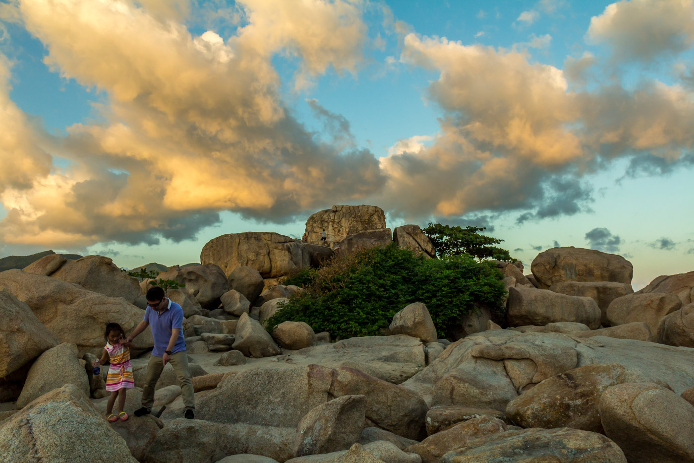 A father and daughter explore the rocks.