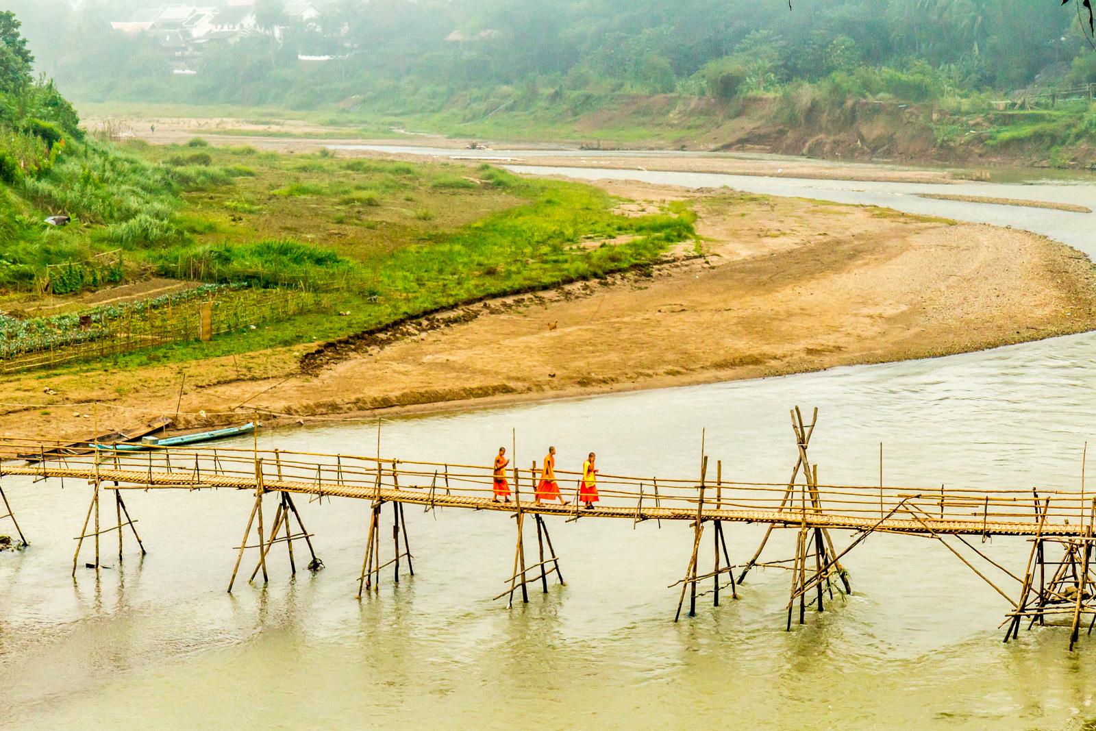 Monks crossing the bamboo bridge.